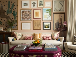 """A plain sofa is the canvas for Rosie's love of layering, here she uses prints, posters, a sketch by her grandmother and pieces of textiles as the foundation of her gallery wall, she used online framers, Picture Frame Express, as the wide selection and price make creating a gallery wall affordable. """"Getting the scale of furniture right is key, after that use cushions, art and books, that is where you can layer and bring in lots of different textures and colours. We make our own cushions at Rosanna Bossom from fabric offcuts. You can stumble across a bargain without actively looking for it."""""""