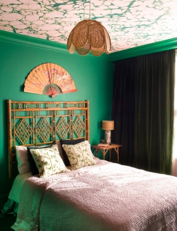 The marbled ceiling created curtesy of P&B wallpaper, Margate Marble in Emerald Pinky, bamboo bedhead, bedside table, lampshade and fan all come together to provide the Chinese theme Whinnie was inspired to create in this bedroom.