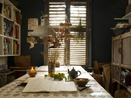 Intensely painted dark walls, closed wooden shutters, candle-light and the natural world inspire illustrator Jude Wisdom. The dining room is where Jude works on her illustrations. The darkness inside keeps the world outside at bay.