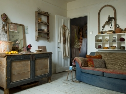 A vintage French nightshirt is used as decoration on the door into the sitting room, Jude picks them up from the flea market. Her collection of treasures; coral, a birds nest, pebbles and more branches are displayed.