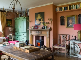 """The Georgian fire surround was found at auction at a country estate in the Cotswolds, """"the family never had any heating as there was no cash, so they sold some of their stuff, to pay for central heating"""". The coffee table holds an 18th century bread rack piled with reference books. The wrought iron chandelier is Lucy's mothers and the painting above the fireplace is, think Andy and Lucy, early to mid-19th century American and depicts a kind of naïve folk art from that era, while the painting to the right is from the 18th century. The Victorian linen press still has its original green paint, which for Andy and Lucy add to its beauty, """"we love the cracked and patinated feel of the old paint for its history and originality."""""""