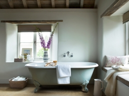 The master bedroom has its own freestanding bath from the Cast Iron Bath company painted in Pigeon by Farrow and Ball, wicker baskets from Neptune store sundries.