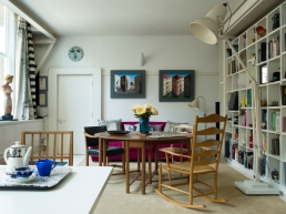 Two Reverspective paintings by Patrick are on display here, flanked by a Fornasetti clock, overlooking an Arts and Crafts table and rocking chair and Charles Eames chairs.