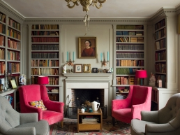 The library and fireplace were designed and built by David in an early American colonial style. The table is from a car boot, the chairs belonged to Juliet's sister, the sheet music Juliet cannot bear to throw away despite the fact that no-one plays. The lamps are recycled car-boot finds.