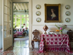 Looking through from the dining room to the sitting room in the French home of Textile Designer & Antique Textile Dealer @susandeliss her hand-block print tablecloth with its rich colours and textures perfectly compliments the antique Tommette floor tiles & sofa beyond...