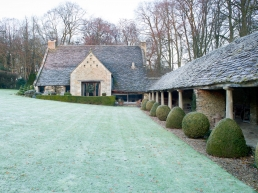 The 1740 barn embellished with a large festive wreath greets festive guests across a frosty garden. Whilst the Grade I listed walkway and its Roman pillars can be seen on the right. The topiary was already fully established when they bought their home.