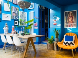 Dining room in the home of Zoe Anderson of W A Green, London. Vibrant blue walls are covered with super stylish artworks, while the dining table oozes character with kitsch Mexican candle holders, a statue of the Virgin Mary and an uber cool cobalt blue Neolit fruit bowl.